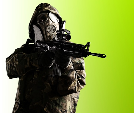 portrait of soldier with mask and rifle over green photo