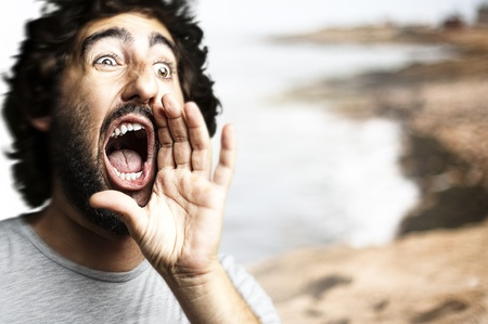 portrait of young man shouting against a beach background photo