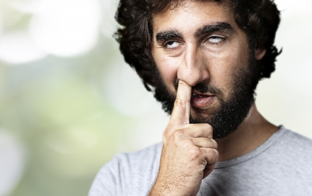 ugly mouth: young man with finger in his nose against a nature background