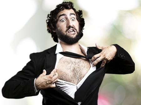 zakenman met moed en Superman begrip scheurt zijn shirt uit tegen een abstracte achtergrond