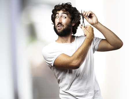 portrait of young man cutting himself hair indoor photo
