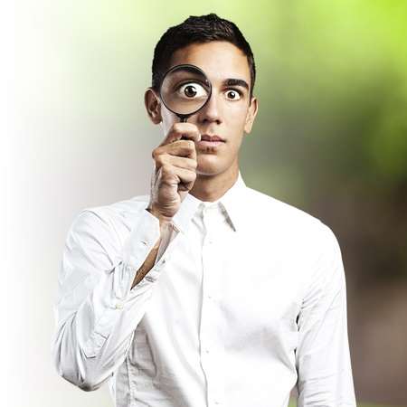 portrait of young man looking through a magnifying glass in the park photo