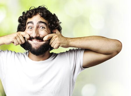 portrait of young man pulling his mouth smiling against a abstract background Stock Photo - 11954917