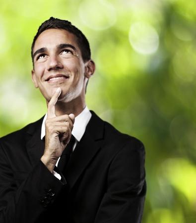 adolescente pensando: Retrato de hombre pensativo joven con una demanda contra un fondo de plantas