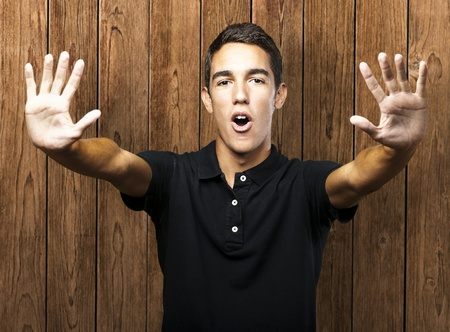 five fingers: portrait of young man doing stop symbol against a wooden wall