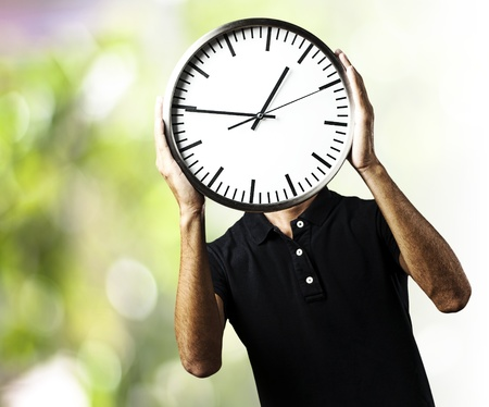 portrait of young man holding a clock with his hands against a nature background Stock Photo - 11954902