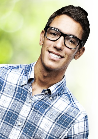 young man portrait: portrait of young student with glasses against a nature background