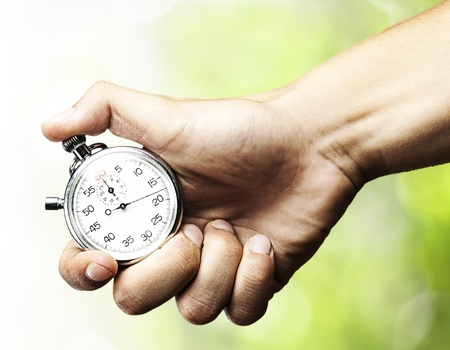 stop time: hand holding stopwatch against a nature background