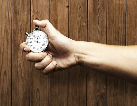hand holding stopwatch against a wooden wall photo