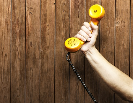 orange vintage telephone against a wooden wall photo