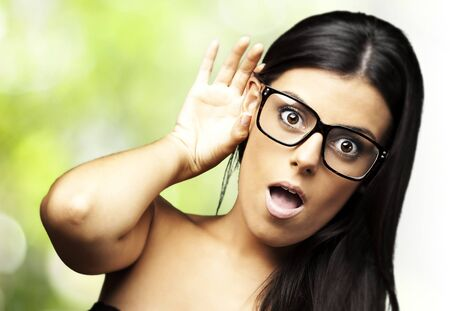 portrait of young woman surprised hearing a sound against nature background photo