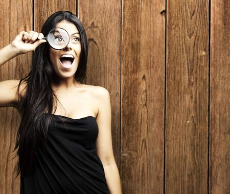 young woman looking through a magnifying glass against a wooden wall photo