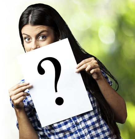 portrait of young woman holding a question symbol against a plants background photo
