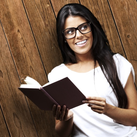 young woman holding book against a wooden wall Stock Photo - 11507832
