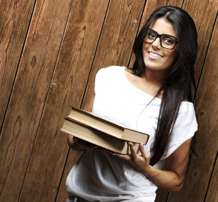 young woman holding books against a wooden wall photo