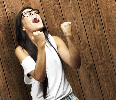 portrait of young woman doing good symbol against a wooden wall woman win gesture against a wooden wall photo