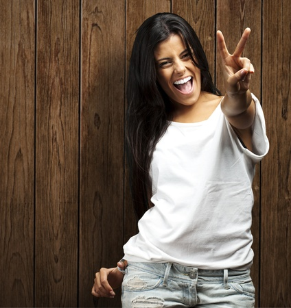 portrait of young woman doing good symbol against a wooden wall photo