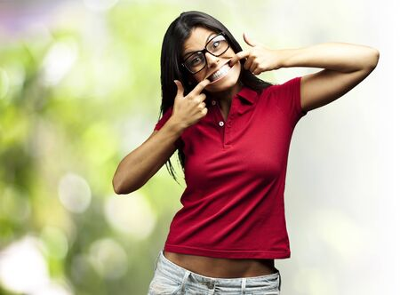 portrait of a happy young woman gesturing with the mouth against a nature background photo