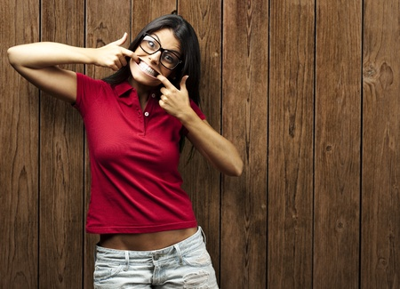 portrait of young woman gesturing happy against a wooden wall photo
