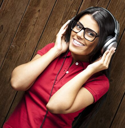 portrait of young woman listening music against a wooden wall Stock Photo - 11507854