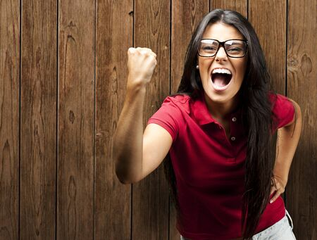 portrait of yougn woman win gesture against a wooden wall Stock Photo - 11507955