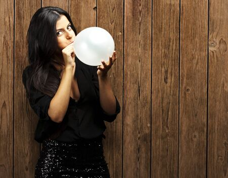 portrait of young woman blowing balloon against a wooden wall photo