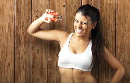 portrait of sporty young woman doing excercise against a wooden wall photo