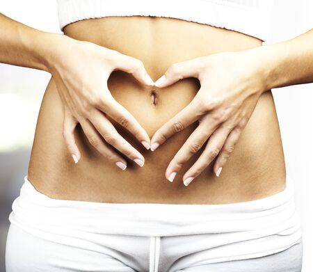 young woman doing heart symbol on her belly button indoor