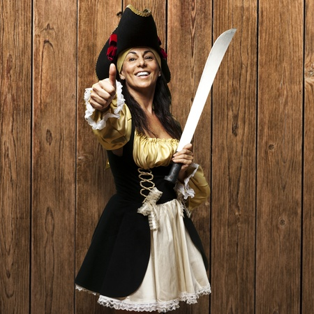 pirate woman holding sword against a wooden wall photo