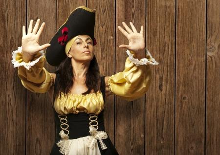 mujer pirata: mujer pirata señalando tope contra una pared de madera Foto de archivo