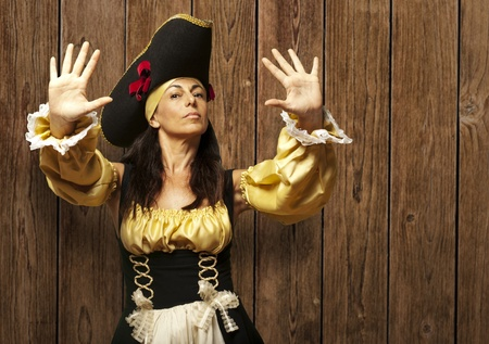 pirate girl: pirate woman gesturing stop against a wooden wall