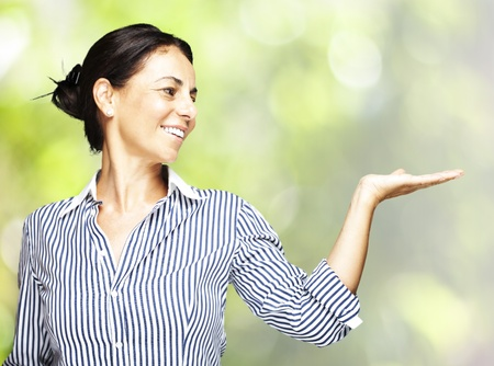 portrat of a middle aged woman holding gesture against a nature background Stock Photo - 11507848