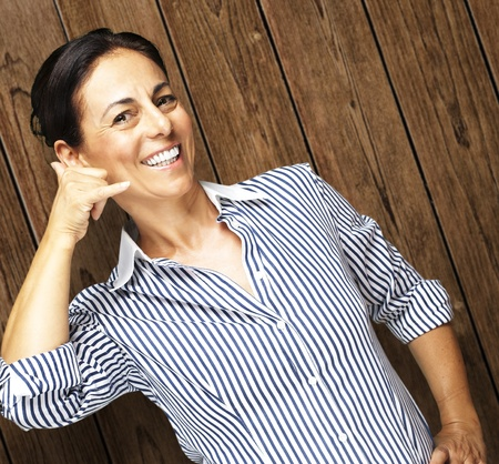 portrait of middle aged woman holding gesture against a wooden wall Stock Photo - 11507889