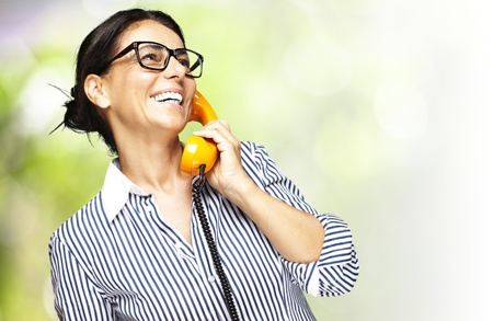 portrait of a middle aged woman talking on vintage telephone against a nature background photo
