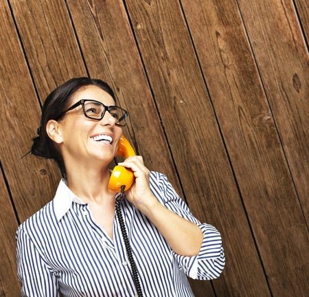 portrait of middle aged woman talking on vintage telephone against a wooden wall photo