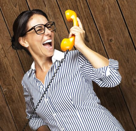 portrait of middle aged woman talking on vintage telephone against a wooden wall Stock Photo - 11507874