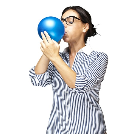 portrait of middle aged woman blowing a balloon over white background photo