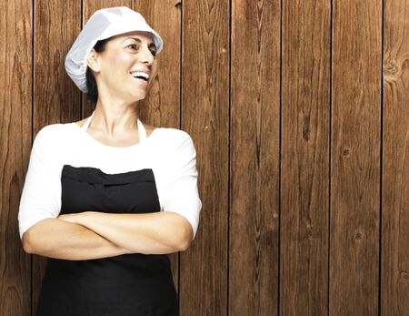 chef uniform: portrait of middle aged woman smiling against a wooden wall