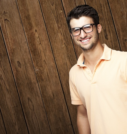 portrait of young man smiling with glasses against a wooden wall photo
