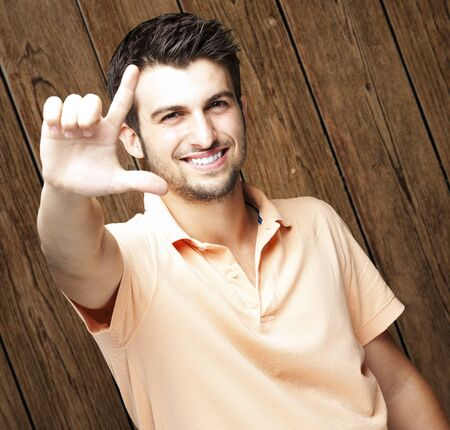 young man doing good symbol against a wooden wall Stock Photo - 11507865