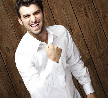 portrait of young man gesturing win against a wooden wall Stock Photo - 11507810