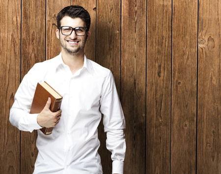 portrait of young man holding book against a wooden wall photo