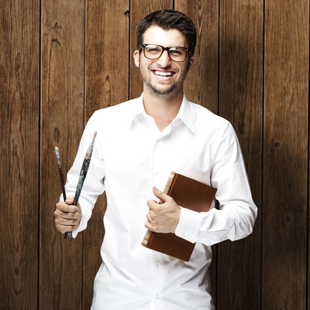 portrait of young man holding books against a wooden wall photo