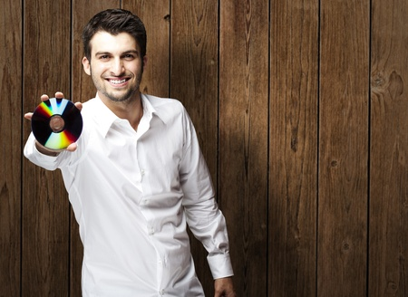 portrait of young man holding cd against a wooden wall Stock Photo - 11507903
