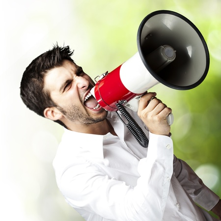 portrait of young man shouting using megaphone against a nature background photo