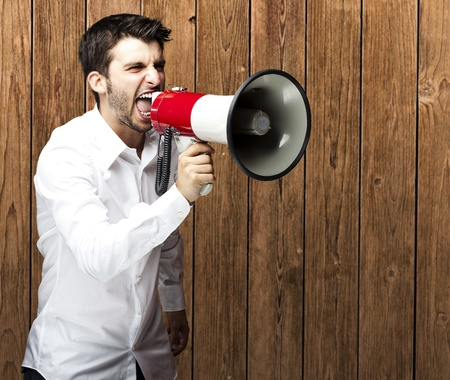 portrait of young man shouting with megaphone against a wooden wall Stock Photo - 11507958