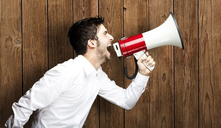portrait of young man shouting with megaphone against a wooden wall Stock Photo - 11507895