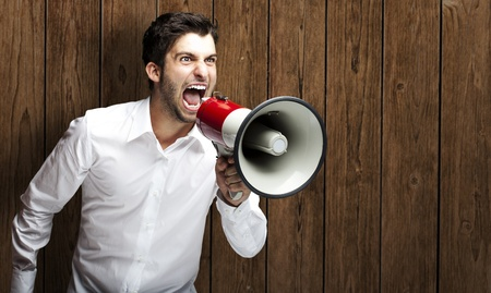 portrait of young man shouting with megaphone against a wooden wall photo