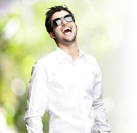 portrait of a handsome young man wearing sunglasses and enjoying against a nature background photo