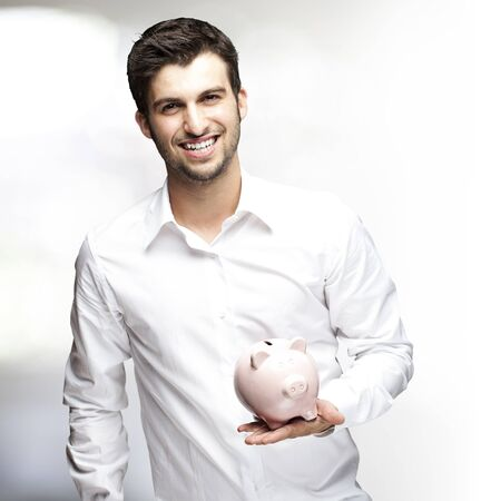 portrait of young man holding piggy bank indoor photo